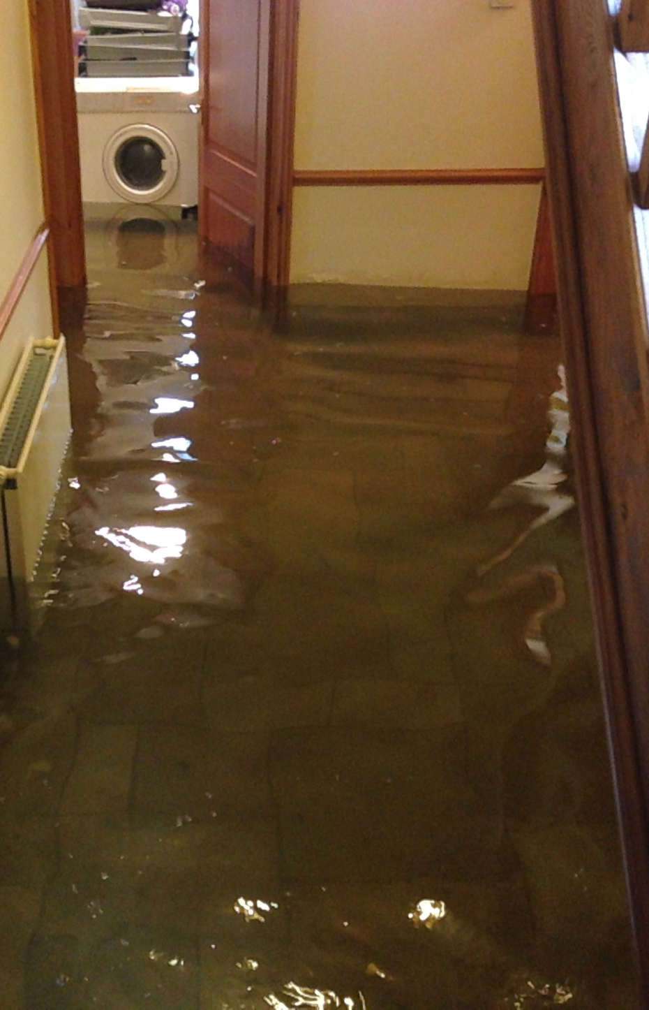 Flooded hallway with washing machine visible